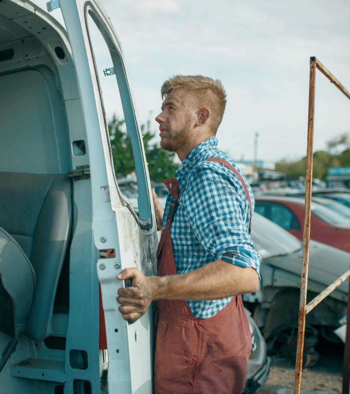 Male repairman removes the door on car scrapyard